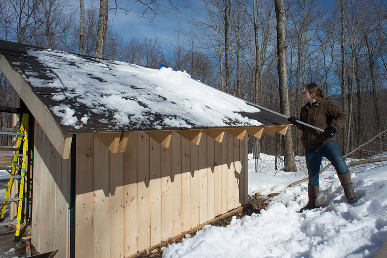 Tara Raking Snow off Solar Shed Roof