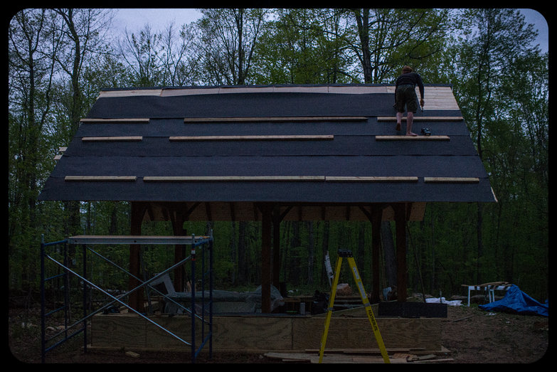 Tyler Affixing Tar Paper to Cottage Roof in the Early Morning