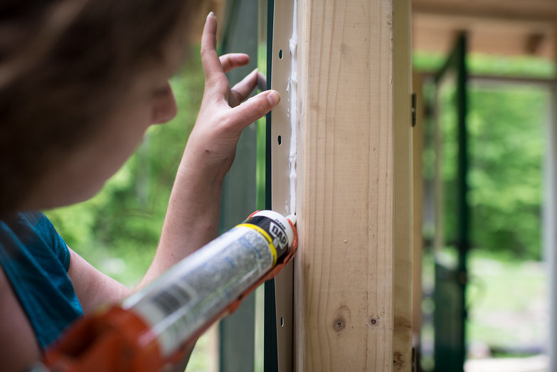 Tara Adding Caulk to Windows