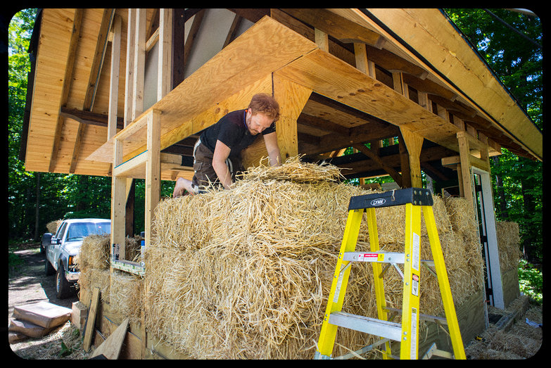 Tyler Stuffing Holes in Third Course of Straw Bales