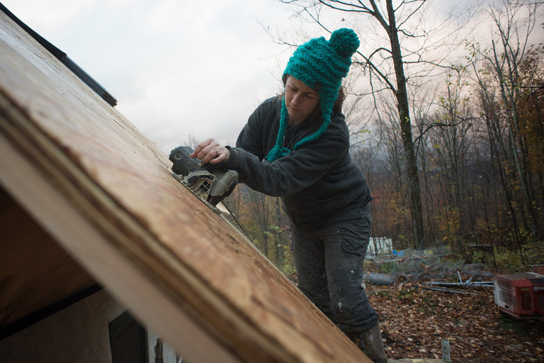 Tara Cutting Excess Plywood on Cottage Roof