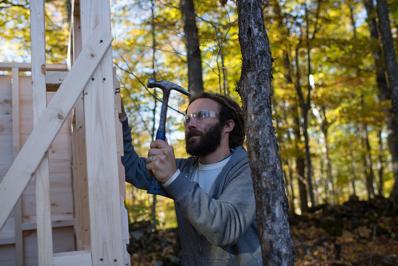 Shlomy Affixing Siding to Outhouse