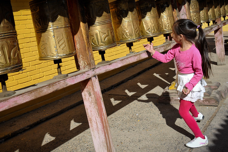 Girl Spinning Prayer Wheels