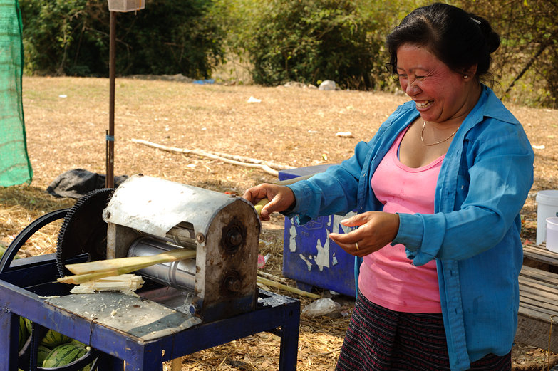 Smiley Lao Lady Juicing Sugarcane