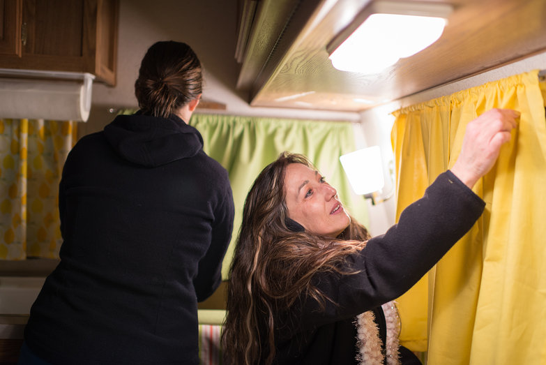 Tara and Jodi Hanging Curtains in Our Camper