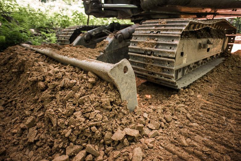 Excavator Blade Pushing Driveway Stone