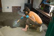 Camille Applying Oil Mixture on Earthen Floor